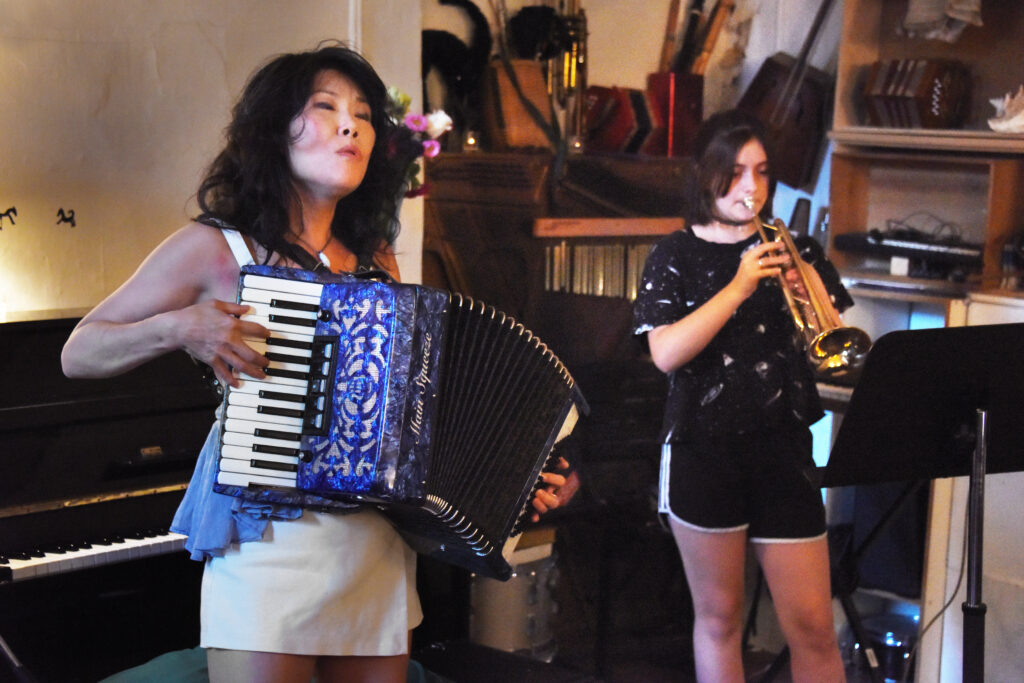 """Lila Eaton on trumpet and Susan Hwang on accordion at the video release event for """"Psalm to Aviation 58"""" based on the poem by Serhiy Zhadan.  The release event included live performances from Susan Hwang with Marlon Cherry on percussion and Lila Eaton on trumpet."""